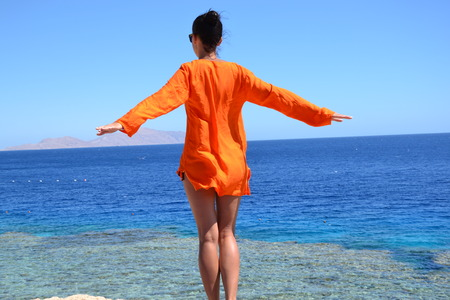 stands: The girl on the sea in orange, stands on the shore and looks into the distance on the rocks and catch the summer breezes.