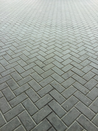 Gray brick wall on horizontal.Grey color photo of a brick close up on the wall