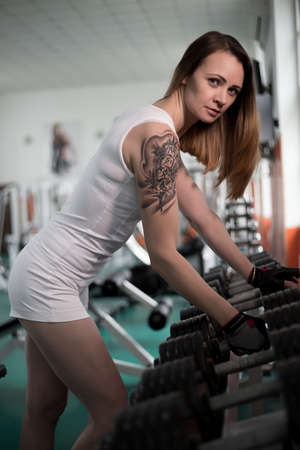 engaged: Young beautiful girl is engaged in fitness with dumbbells Stock Photo