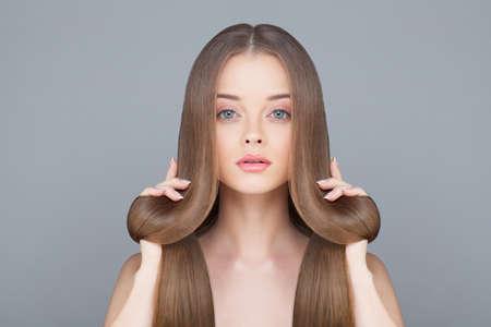 水色の背景で健康的な髪の女性