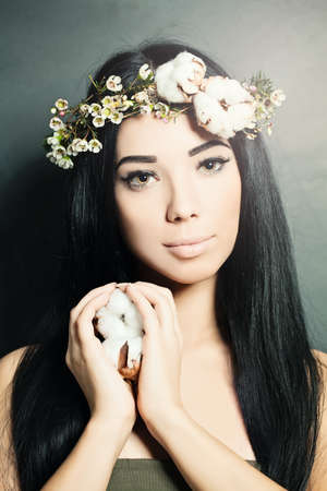 Beautiful brunette woman with cotton flowers in her hair and hand. Stock Photo