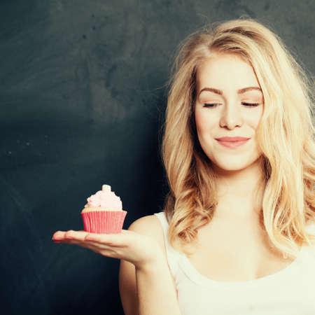 Schöne lächelnde junge Frau mit einem Kuchen Standard-Bild - 65439982