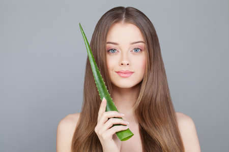 Woman with Clear Skin and Long Healthy Hair Holding Green Aloe Leaf Stock Photo