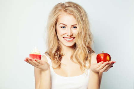 Smiling Woman with Healthy and Unhealthy Food.