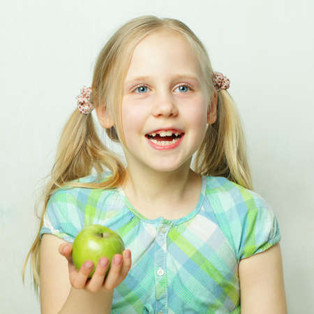 Laughing little girl with green apple Stock Photo