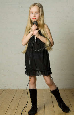 Young girl holding microphone - rock singer