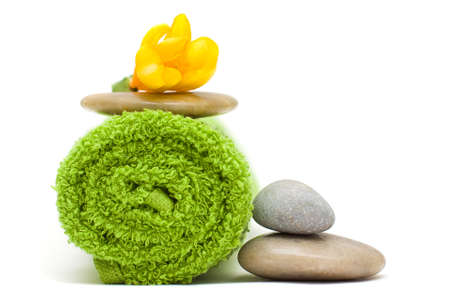 Yellow flower, green towel and river stones - harmony spa concept Stock Photo
