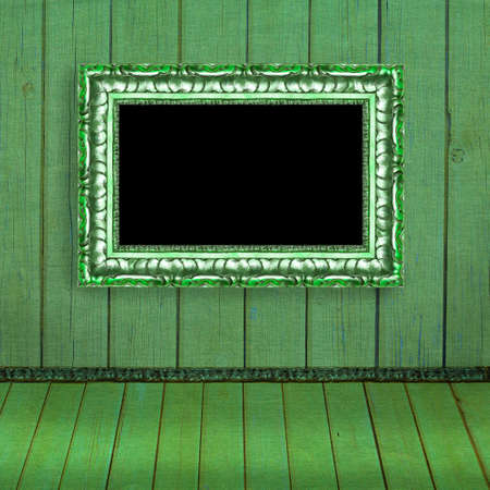 Photo frame hanging on the green blurred wall - old album background
