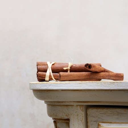 spicey: Brown cinnamon sticks lie on the vintage wooden desk Stock Photo
