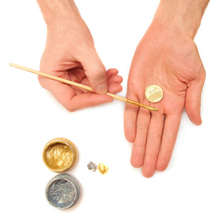Make money. Concept. Hands, coins, gold and silver paint on a white background