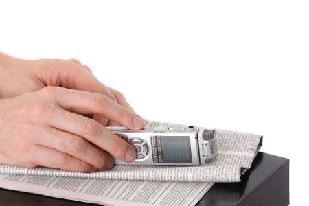 Diktafon in male hand and newspaper on black table isolated on white background Stock Photo