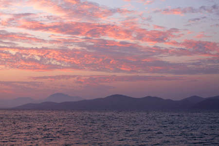 Magnificent sunset on sea, Greece. Clouds and reflexions on water