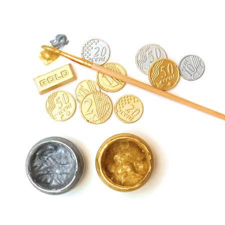 Gold reserve. Concept. Bullion, coins, brush, gold and silver paint cans Stock Photo