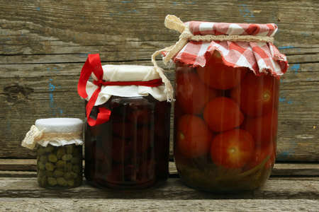 preserves: Jar with preserves. Homemade strawberry jam, pickled tomatoes and capers on wooden background