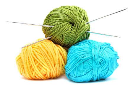 Ballen van wol met breinaalden op een witte achtergrond