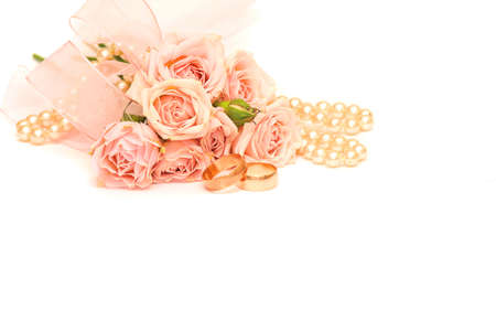 fiancee: two golden rings, pearls and delicate roses on white background