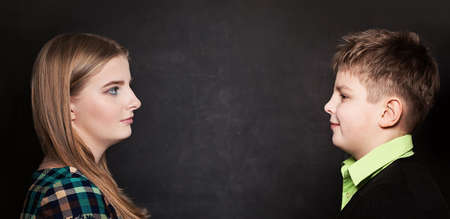 Young Boy and Girl Looking Each Other on Blackboard Background. Profile 版權商用圖片