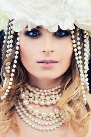 Beautiful Woman Fashion Model with White Pearls and Flowers. Glamorous Beauty, Face Closeup Stock Photo