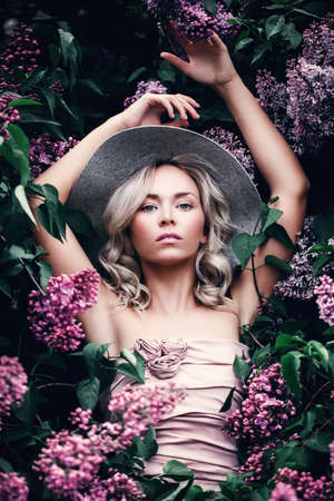 Perfect Blonde Model in Spring Flowers Garden. Beautiful Woman with Healthy Skin, Beauty Hairstyle and Fashionable Hat