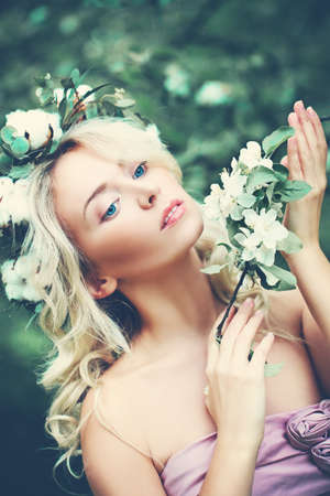 Spring Beauty. Young Woman with Blonde Curly Hairstyle and Flowers Outdoors Stock Photo