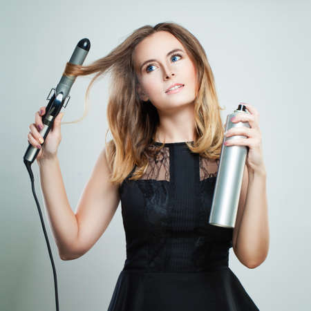 Glamorous Woman with Blonde Wavy Hair Ironing It, Using Curling Iron. Happy Girl With Gorgeous Healthy Smooth Hair Using Curler For Perfect Curls. Hairstyle And Hairdressing