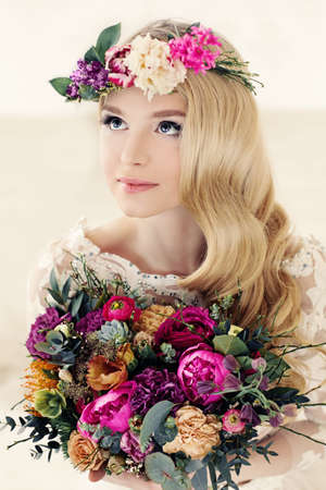 Beautiful Blonde Bride and Colorful Flower Arrangement. Woman with Flower Wreath, Bridal Curly Hairstyle and Makeup