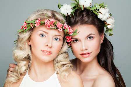 Beautiful Women with Permed Hairstyle, Makeup and Flowers. Young Beauty