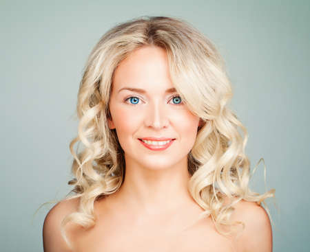Smiling Model Woman with Blonde Curly Hair. Friendly Face Stock Photo