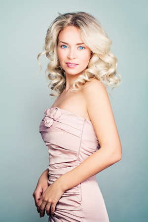silky hair: Beautiful Blonde Fashion Model Woman with Curly Hair and Makeup Wearing Pink Silky Dress Stock Photo
