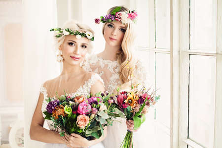 Two Perfect Bride. Blonde Women with Flower Arrangement, Flower Wreath, Wedding Hairstyle and Makeup Stock Photo
