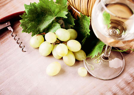 Wine, Glass, Grape and Grapevine with Green Leaves on Rustic Wooden Board Background Stock Photo