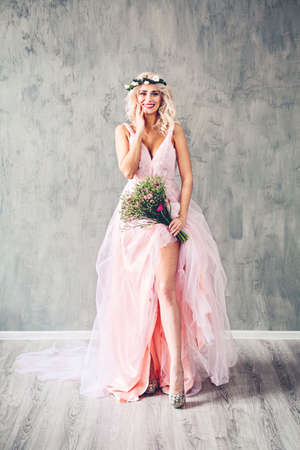Laughing Sexy Woman in Evening Gown. Happy Model Girl with Flowers