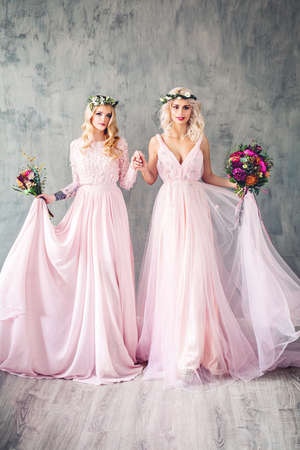 Beautiful Blonde Women in Pink Evening Gown Smiling. Perfect Hairstyle, Makeup and Summer Flowers