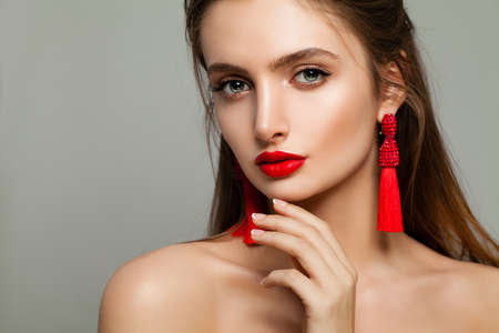 silky hair: Young Woman with Red Lips Makeup and Jewelry Earrings. Beautiful Model, Cute Face Stock Photo