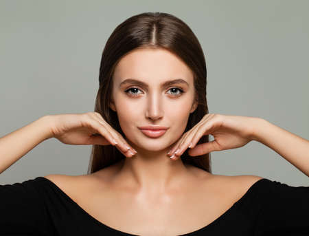 Perfect Young Model Woman with Healthy Skin, Shiny Hair and Manicured Hands on Background. Young Beauty, Facial Treatment and Cosmetology Concept