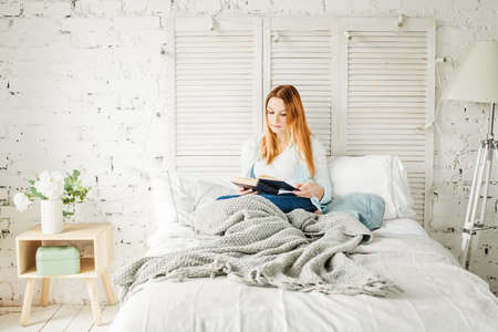 Cute Redhead Woman Reading Book at Home with Grey Woolen Blanket