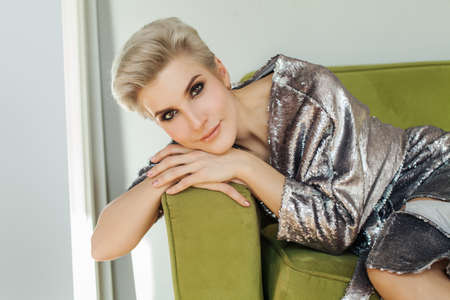 Belle femme blonde aux cheveux courts, assise sur un canapé vert. Visage de femme parfait
