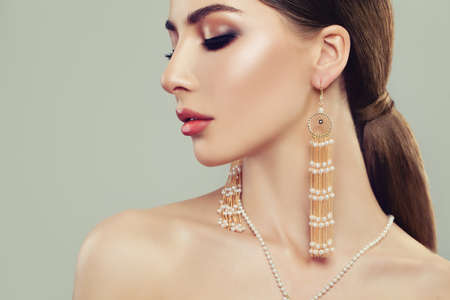 Glamorous Woman with Gold Jewelry Earrings with White Pearls on Banner Background Archivio Fotografico