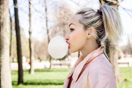 Young woman blowing bubble with chewing gum and walking in park outdoors, lifestyle portrait