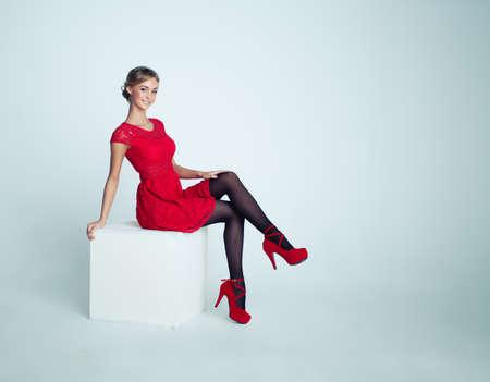 Gelukkige vrouw in rode jurk op witte achtergrond Stockfoto
