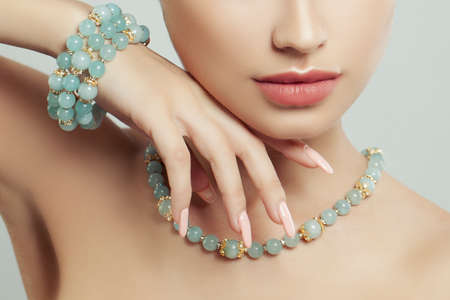 Perfect jewelry on female body, closeup portrait. Bracelet, necklace and manicure
