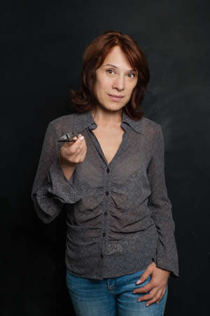Mature business woman smiling, holding glasses and pointing Stock fotó