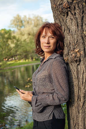 Mature woman with smartphone relaxing in park outdoors. Woman cell phone