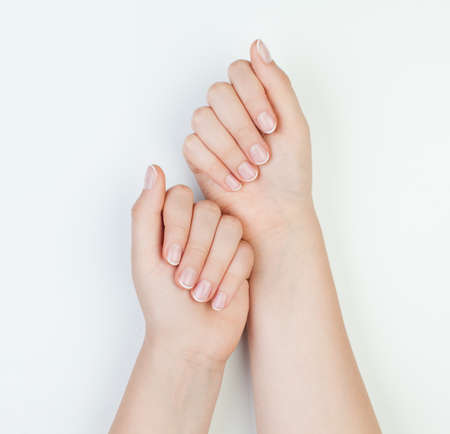 Beautiful female hands together on white background. Manicure concept