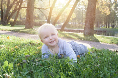 Kid lying on the green grass outdoor. Little child boy portrait