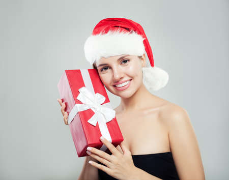 Cheerful woman in red Santa hat and Christmas gift box