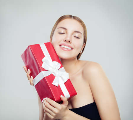 Beautiful woman fashion model holding red gift and smiling Stock Photo