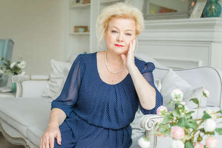 Portrait of blonde older woman at home, 60 years old
