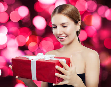 Smiling woman holding red gift on bokeh background Stock fotó