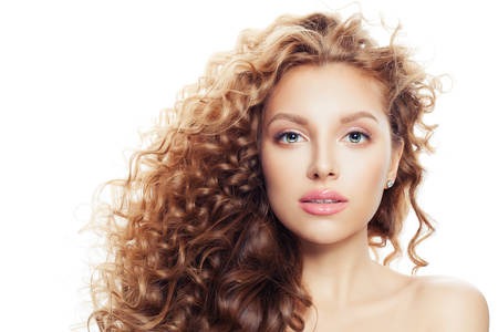 Young woman with clear skin and long curly hairstyle isolated on white Imagens